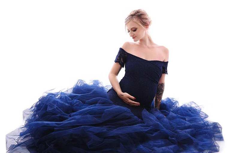 Femme enceinte en robe de princesse bleue assise sur le sol