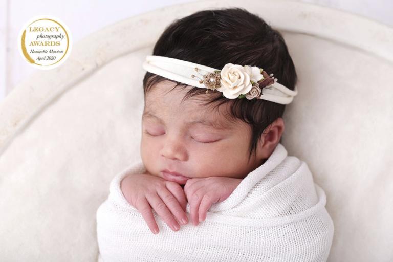 Nouveau-né emmailloté dormant en séance photo