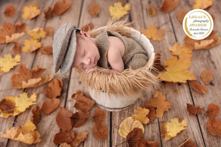 Nouveau-né dormant dans un sceau en séance photo