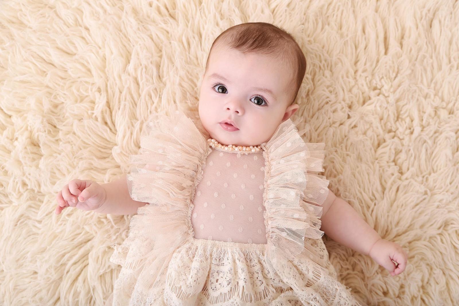 Bébé en robe vintage allongé sur un flokati