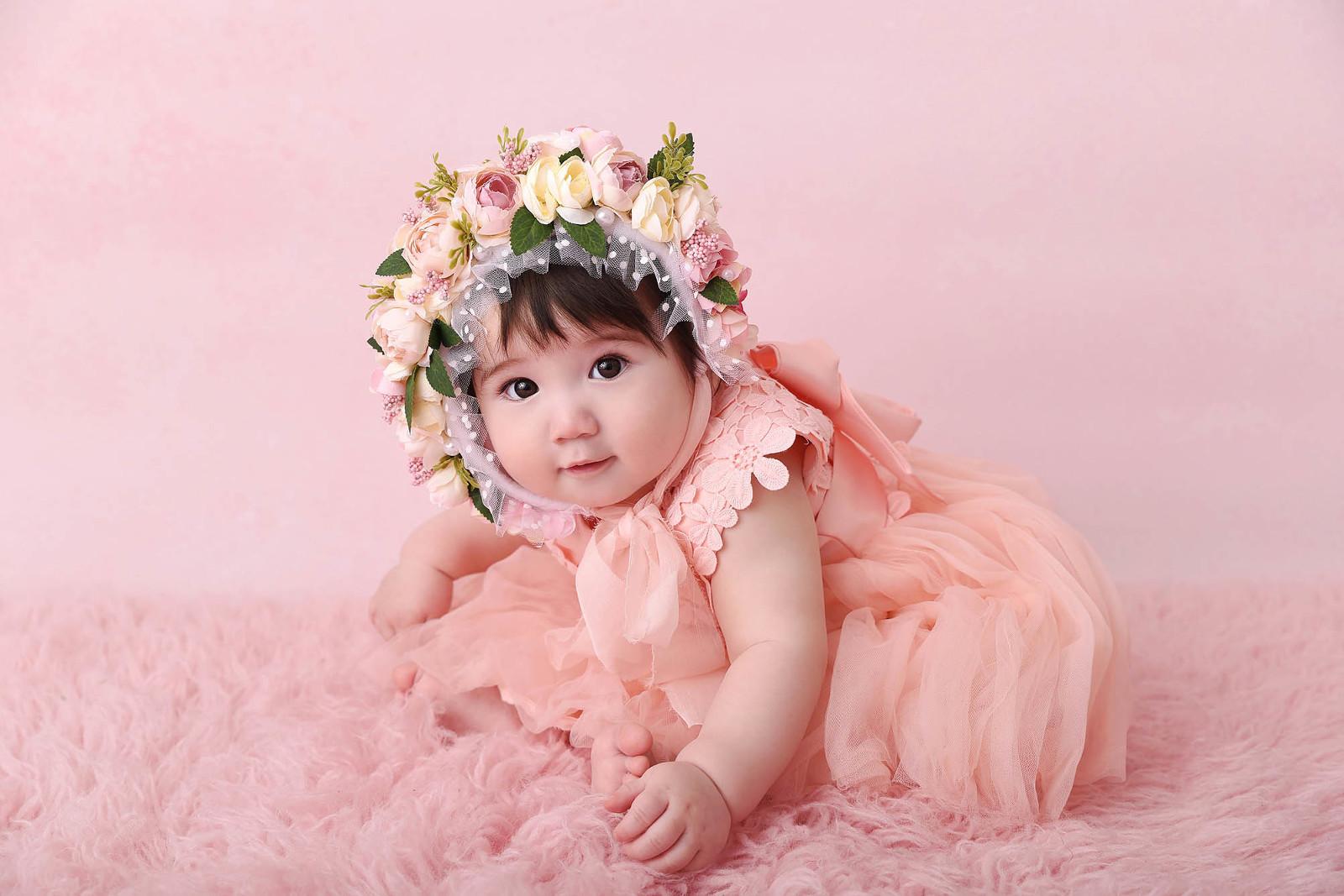 Bébé en robe rose avec un bonnet à fleurs