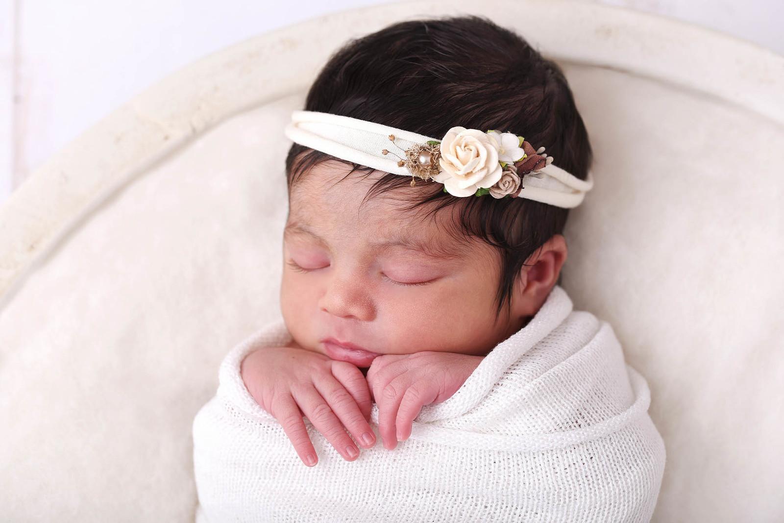 Bebe emmailloté dormant avec un bandeau à fleurs